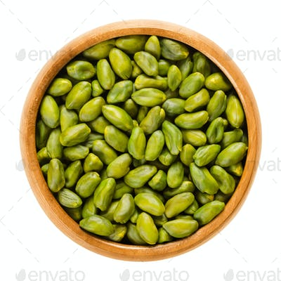 Green pistachio seeds in wooden bowl over white