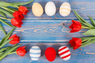 Bouquet of red tulips and Easter eggs wrapped woolen string, festive decoration