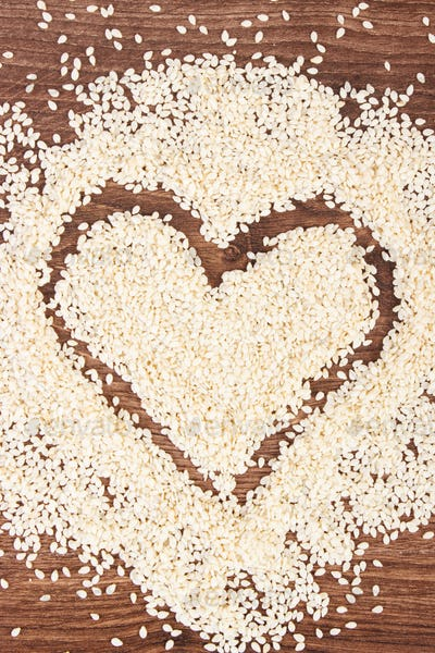 Heart of sesame seeds on board, healthy nutrition concept and sumbol of love
