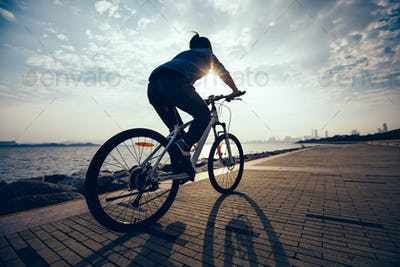 silhouette of woman cycling on seaside during sunrise