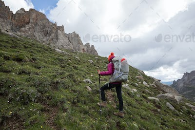 Woman hiker with heavy backpack ascent on high altitude mountain