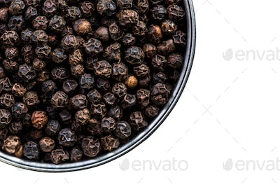 Black pepper seeds in pot isolated on white