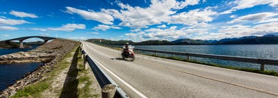 Biker rides a road with Atlantic Ocean Road in Norway.