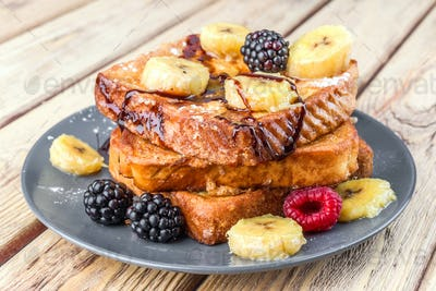 Tower of french toast with fried plantain and berries in natural wood