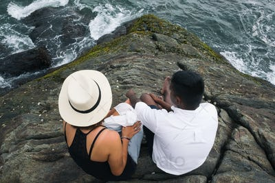 Man and woman siting on cliff together and looking on ocean water