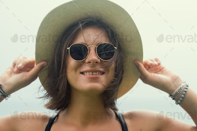 Close up shot of stylish caucasian young woman in sunglasses smiling
