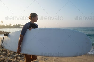 caucasian woman with surfboard standing near water and looking at waves.