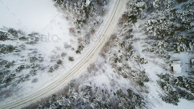 Aerial view of a winter road. Winter landscape countryside. Aerial photography of snow forest.