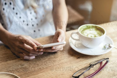 Young woman using smart phone and drinking coffee in cafe