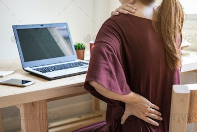 Young woman working at home and having back pain