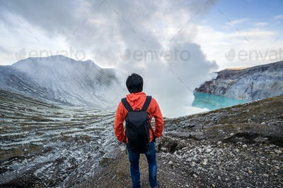 Young travler looking crater blue lake at Kawah Ijen, Indonesia
