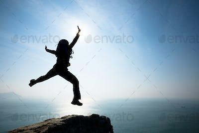 Hipster backpacker jumping on sunrise seaside cliff edge