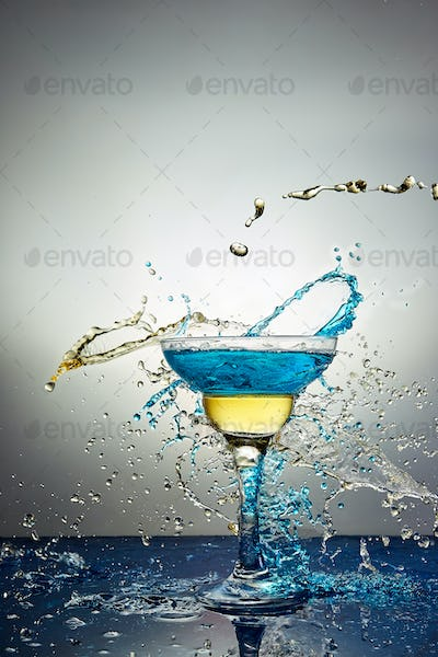 Glass with blue and yellow  champagne or cocktail. Levitation
