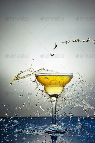 Glass with yellow champagne or cocktail. Levitation