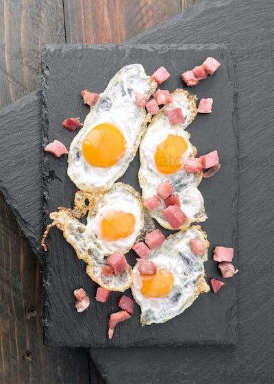 overhead shot fried quail egg with baked ham on black stone