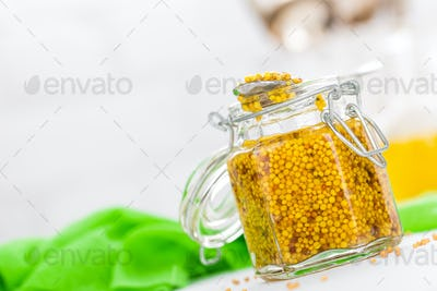 Mustard in glass jar on white wooden table closeup. Dijon mustard