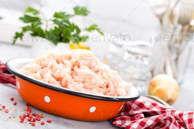 Forcemeat. Raw ground chicken meat in bowl on white kitchen table. Fresh minced chicken breast meat