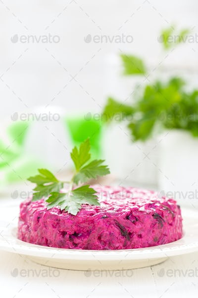 Salad of boiled beet. Beetroot salad with prune, walnuts and sour cream on white background