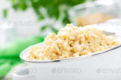 Bulgur wheat. Boiled bulgur cereal in pot on white kitchen table. Healthy vegetarian food