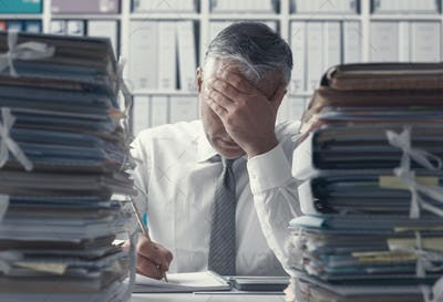 Stressed business executive and piles of paperwork