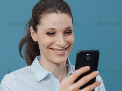 Smiling woman connecting with her smartphone