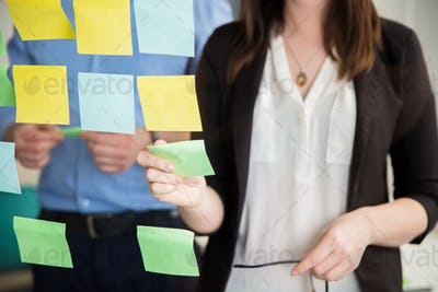 Midsection Of Businesswoman Sticking Note On Glass By Executive