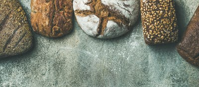 Top view of bread loaves over grey background, wide composition