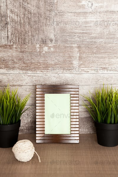 Beautiful photo frame next to two pots of grass