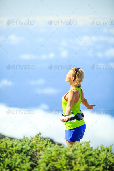 Happy woman runner arms raised outstretched