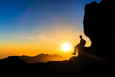 Man hiking silhouette in mountains sunset freedom