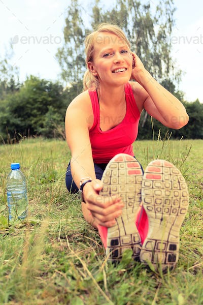 Woman runner exercising and stretching, summer nature outdoors