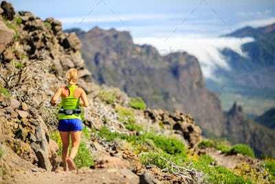 Young woman running or hiking in mountains