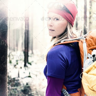 Woman hiking camping in vintage winter forest sunlight