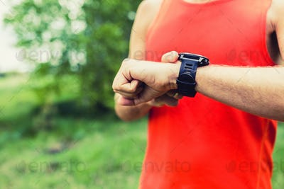 Man running and checking sport smart watch