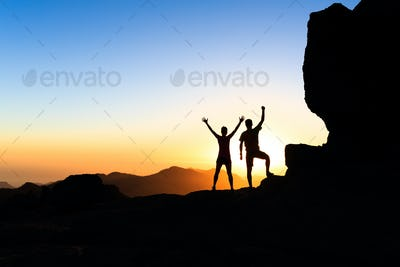 Couple hikers success concept in mountains