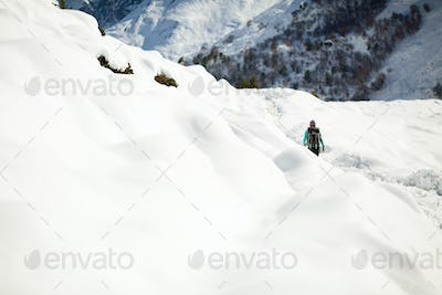 Woman hiking in white winter mountains