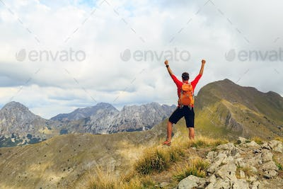 Hiking success, man runner in mountains
