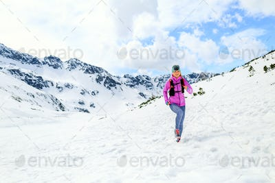 Woman running in mountains in inspirational winter landscape