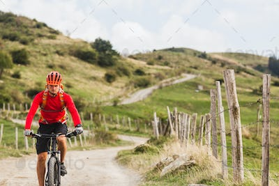 Man riding mountain bike on country road