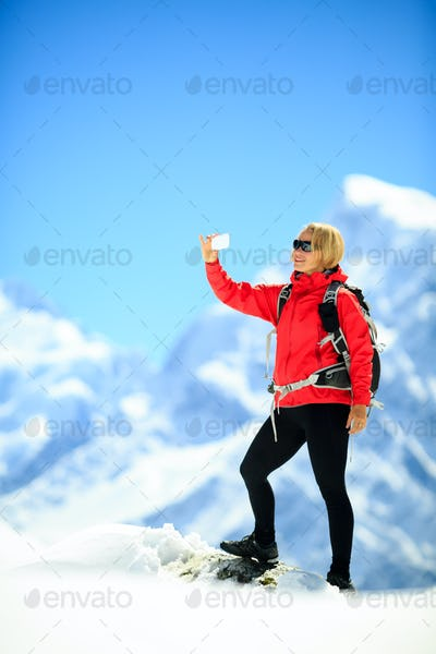 Woman doing smartphone selfie in mountains