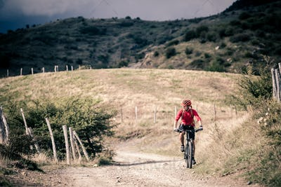 Mountain bike rider on country road, track trail in inspirationa