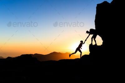 Teamwork couple climbing helping hand