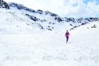 Happy woman running in mountains on winter sunny day
