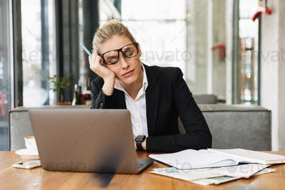 Tired blonde business woman sitting by the table in cafe