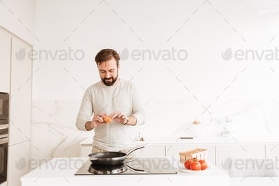 Photo of european man with short brown hair and beard cooking om