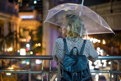 Blond woman taking cover under her umbrella