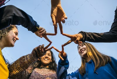 Group of friends using fingers to form the star shape teamwork and support concept