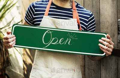 """A person holding an """"open"""" sign"""