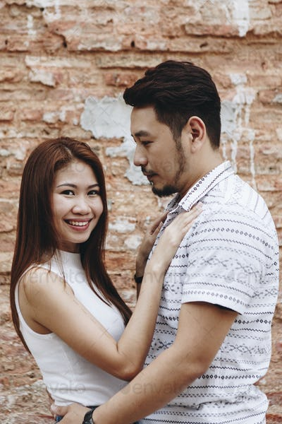 Lovely asian couple by a brick wall