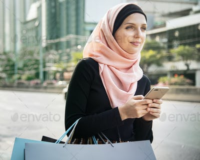 Islamic woman with shopping bags and holding mobile phone